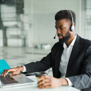 African american customer support operator with hands-free headset working in the office.